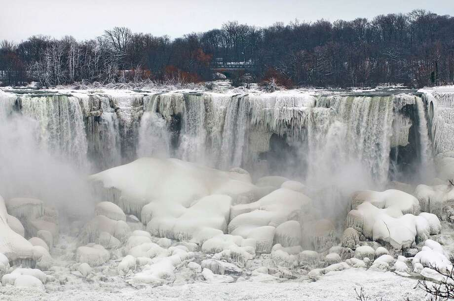 Ice forms along the areas of Niagara Falls and Niagara Falls State Park in Niagara Falls, N.Y., photographed from Niagara Falls Ontario, Canada.  Niagara Falls hasn't frozen over, but it has become an icy spectacle, thanks to a blast of arctic wind and cold that blew around and froze the mist on surfaces and landscaping. Despite the urban legends, Niagara Falls doesn't freeze solid in the winter, tourism officials say.  A section of the American Falls, one of three waterfalls that make up the natural attraction, has frozen. The Niagara River rapids and larger Horseshoe Falls continue to flow unimpeded.  (AP Photo/The Niagara Gazette, James Neiss)  Photo: JAMES NEISS, AP  / JAMES NEISS2014