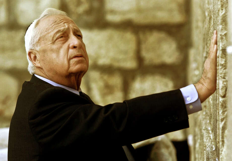 "In this Wednesday Feb. 7, 2001 file photo, Ariel Sharon, then Israel's Prime Minister-elect, looks up as he touches Judaism holiest site, the Western Wall, in Jerusalem. The son of former Israeli Prime Minister Ariel Sharon says his father has died on Saturday, Jan. 11, 2014. The 85-year-old Sharon had been in a coma since a debilitating stroke eight years ago.  His son Gilad Sharon said: ""He has gone. He went when he decided to go."" Photo: David Guttenfelder, AP  / AP2014"