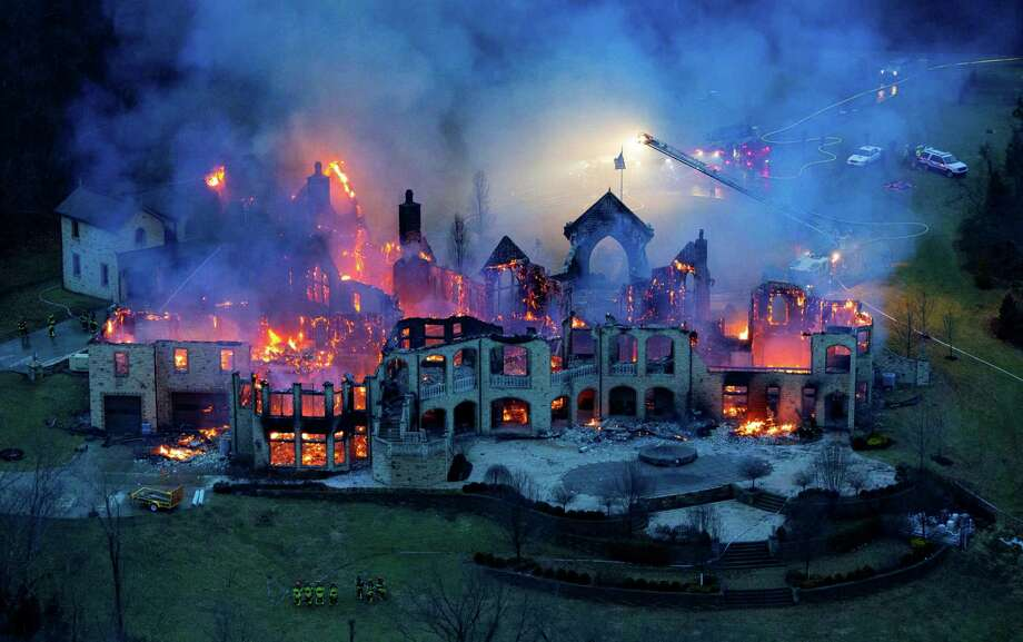 This aerial photo shows firefighters battle a fire at a mansion in Indian Hill, Ohio on Friday, Jan. 10, 2014.   Fire officials are trying to determine what caused the massive fire that destroyed the 22-room mansion in southwest Ohio. There were no injuries reported. Fire officials remained on the scene Saturday. Lt. Jim Gilligan of the Madeira and Indian Hill Joint Fire District says the home was a complete loss. He said it took firefighters about seven hours to put out the fire reported Friday afternoon at the mansion in the Cincinnati suburb of Indian Hill. (AP Photo/The Cincinnati Enquirer, Joseph Fuqua II)  Photo: Joseph Fuqua II, AP  / The Cincinnati Enquirer