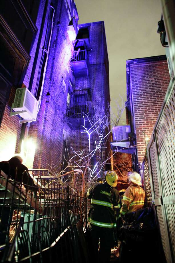 Firefighters look up at the fire escape landing that collapsed around midnight Saturday in the Rittenhouse Square section of Philadelphia, Sunday, Jan. 12, 2014. Authorities say three people were injured, one critically, when a fire escape landing collapsed and fell four stories. Photo: Joseph Kaczmarek, AP  / FR109827 AP