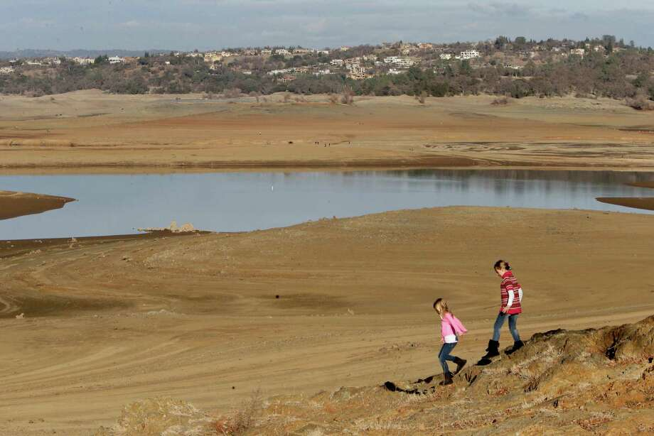 With the edge of Folsom Lake, Calif.,  more than 100 yards away, Gina, 8, left, and Sydney, 9, Gerety walk on rocks that are usually at the waters edge,  Thursday Jan. 9, 2014.  Gov. Jerry Brown said he would meet Thursday with his recently formed drought task force to determine if an emergency declaration is necessary as California faces a serious water shortage. Reservoirs in the state have dipped to historic lows after one of the driest calendar years on record. Photo: Rich Pedroncelli, AP  / AP2014