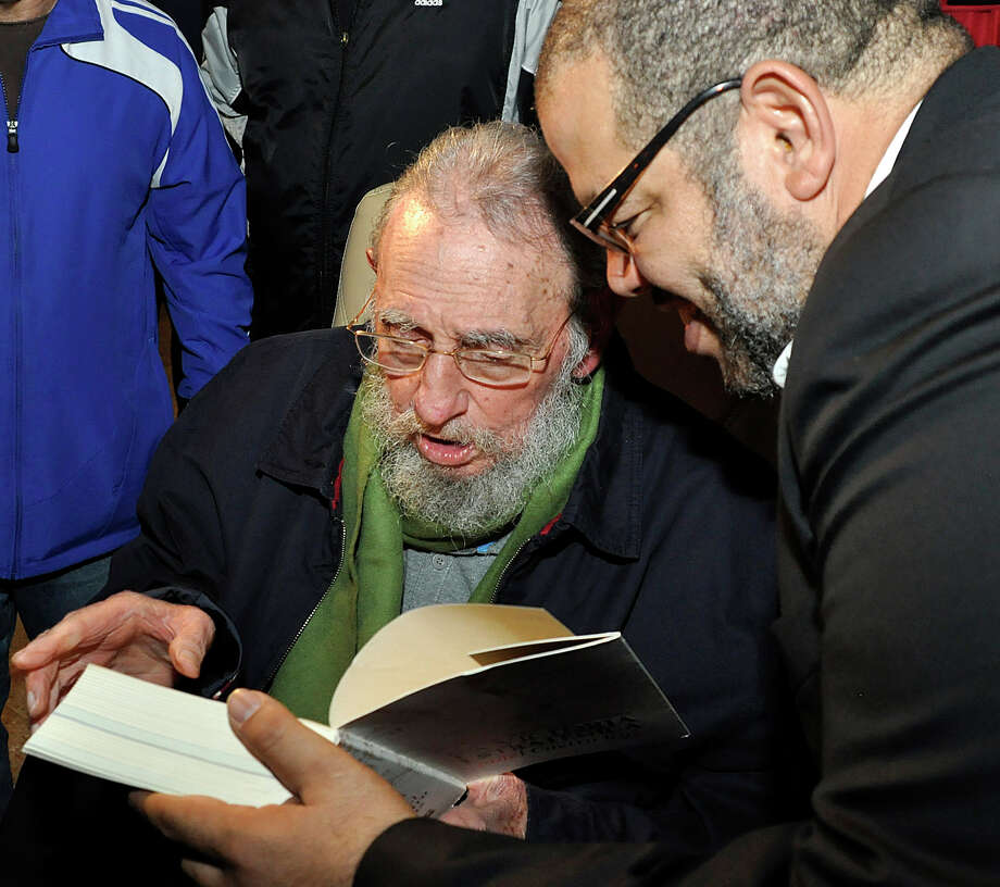 In this photo released by Cubadebate, Cuba's former President Fidel Castro, sitting, dedicates his book to the artist Kcho, right, during the inauguration of the cultural center, Studio Kcho Romerillo, Laboratory for Art, in Havana, Cuba, late Wednesday, Jan. 8, 2014. Castro has made his first public appearance in nine months, attending the opening of the art studio in the Cuban capital. Castro, 87, led Cuba for 48 years before falling gravely ill in July 2006 and handing over power to his brother Raul, who formally became president in January 2008. Photo: Estudios Revolucion, AP  / AP2014
