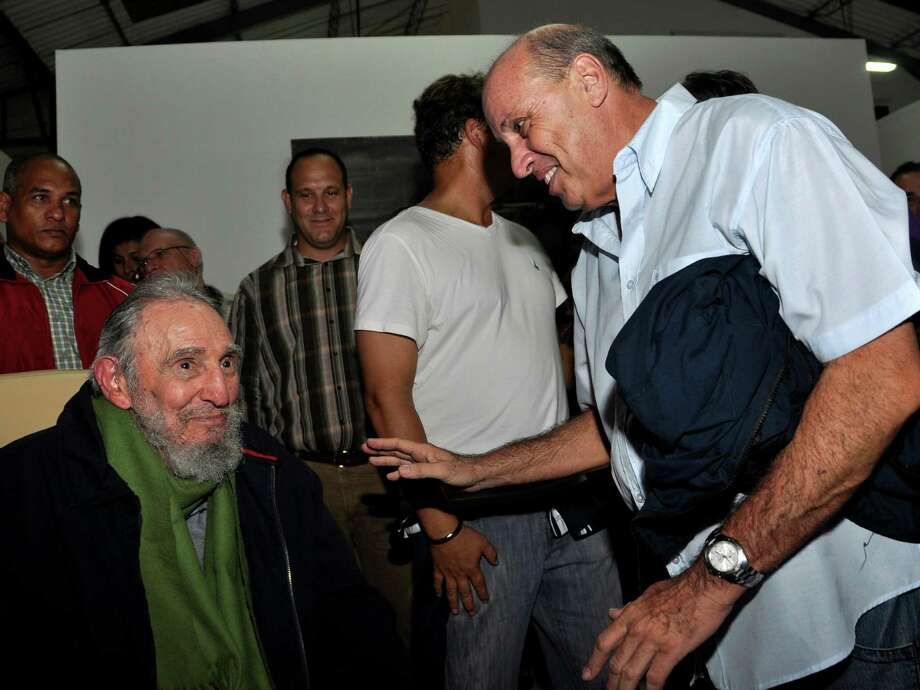 In this photo released by Cubadebate, Cuba's former President Fidel Castro, left, smiles as he visits with Danilo Sirio, president of the Cuban Radio and Television Institute, right, during the inauguration of the cultural center, Studio Kcho Romerillo, Laboratory for Art, in Havana, Cuba, late Wednesday, Jan. 8, 2014. Castro has made his first public appearance in nine months, attending the opening of the art studio in the Cuban capital. Castro, 87, led Cuba for 48 years before falling gravely ill in July 2006 and handing over power to his brother Raul, who formally became president in January 2008. Photo: Estudios Revolucion, AP  / AP2014