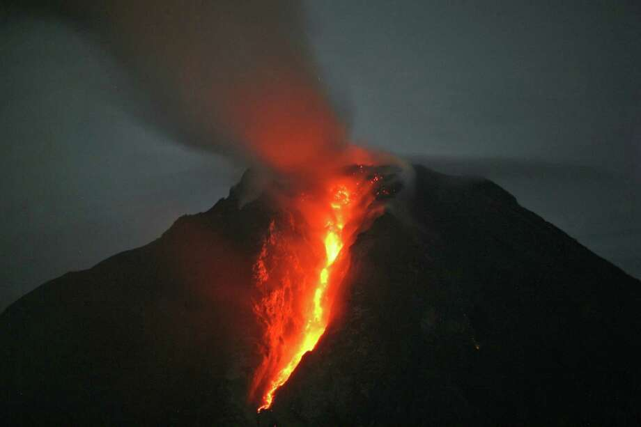 In this late Sunday, Jan. 5, 2014 photo, Mount Sinabung spews hot lava as seen from Jeraya, North Sumatra, Indonesia. The 2,600-meter (8,530-foot) volcano has sporadically erupted since September. Authorities extended a danger zone around a rumbling volcano in western Indonesia on Sunday after it spewed blistering gas farther than expected, sending panicked residents streaming down the sides of the mountain. Photo: Binsar Bakkara, AP  / AP2014