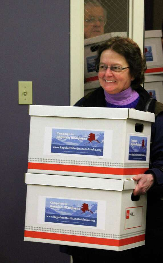 Mary Reff, a sponsor of an initiative to make recreational use of marijuana legal in Alaska, helps deliver more than 46,000 signatures to the state Division of Elections office in Anchorage, Alaska, on Wednesday, Jan. 8, 2014. If the state verifies there are enough valid signatures, the measure will appear on the Alaska primary ballot on Aug. 19, 2014. Photo: Mark Thiessen, AP  / AP