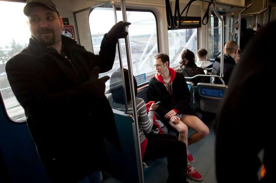 A passenger reacts during Emerald City Improv's No Pants Light Rail Ride on Sunday, January 13, 2013. Dozens of participants took off their pants while riding on the train, shocking some other passengers. Photo: JOSHUA TRUJILLO/SEATTLEPI.COM