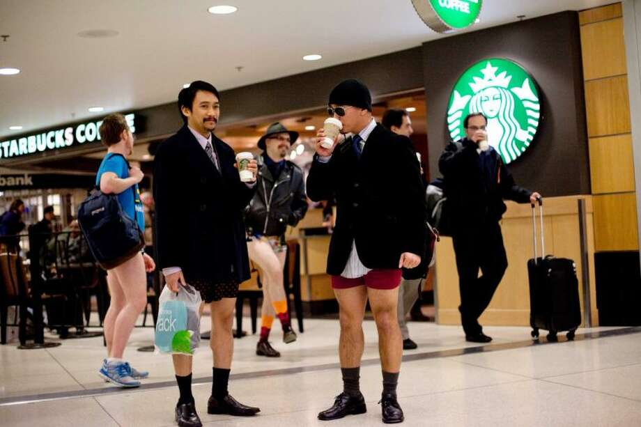 Participants sip coffee in Sea-Tac Airport during Emerald City Improv's No Pants Light Rail Ride on Sunday, January 13, 2013. Dozens of participants took off their pants while riding on the train, shocking some other passengers. Photo: JOSHUA TRUJILLO/SEATTLEPI.COM