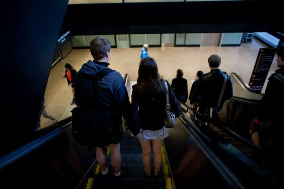 Participants ride an escalator in Sea-Tac Airport during Emerald City Improv's No Pants Light Rail Ride on Sunday, January 13, 2013. Dozens of participants took off their pants while riding on the train, shocking some other passengers. Photo: JOSHUA TRUJILLO/SEATTLEPI.COM