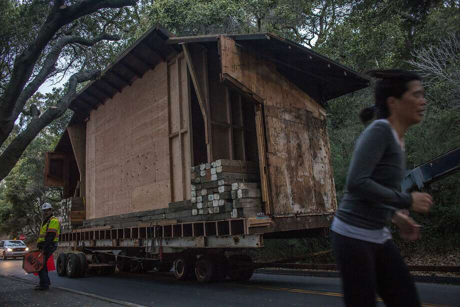 A jogger passes as workers move part of a building designed by Julia Morgan to its new home on the UC Berkeley campus. Photo: Sam Wolson, Special To The Chronicle