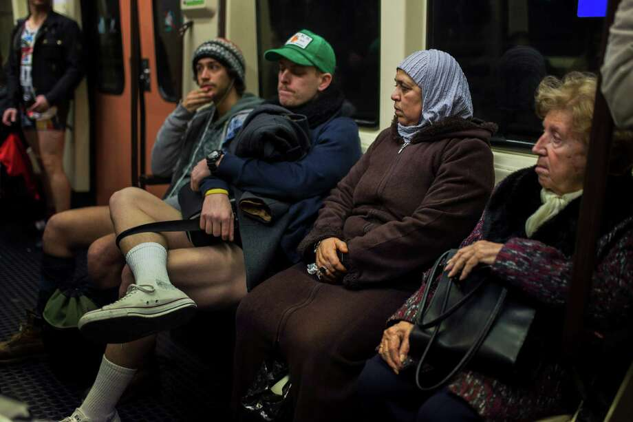 "A Muslim woman looks at participants in the 5th annual ""No Pants Subway Ride"", as they ride the subway without their pants on in Madrid, Spain, Sunday, Jan. 12, 2014. Photo: Andres Kudacki, AP  / AP"