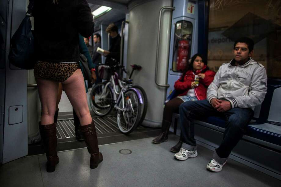 "EDS NOTE - SPANISH LAW REQUIRES THAT THE FACES OF MINORS ARE MASKED IN PUBLICATIONS WITHIN SPAIN - A man sitting next to his daughter looks at a  participant who stand on the train without her pants during the 5th annual ""No Pants Subway Ride"" in Madrid, Spain, Sunday, Jan. 12, 2014. Photo: Andres Kudacki, AP  / AP"
