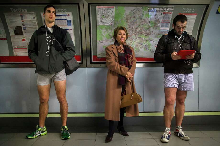 "A passenger stands in between participants as they wait for the train without their pants during the 5th annual ""No Pants Subway Ride"" in Madrid, Spain, Sunday, Jan. 12, 2014. Photo: Andres Kudacki, AP  / AP"