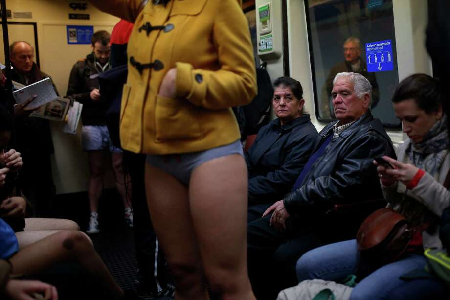 "A man looks at a participant who stands on the train without her pants during the 5th annual ""No Pants Subway Ride"" in Madrid, Spain, Sunday, Jan. 12, 2014. Photo: Andres Kudacki, AP  / AP"
