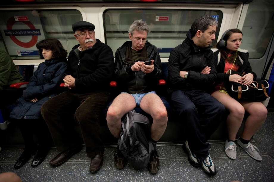 "People take part in the ""No Trousers Tube Ride"" event next to other passengers on an underground train passing through King's Cross station in London, Sunday, Jan. 12, 2014.  The stunt was held to coincide with the ""Global No Pants Subway Ride"", where passengers board subway cars in the middle of winter without wearing trousers and act normally. Photo: Matt Dunham, AP  / AP"