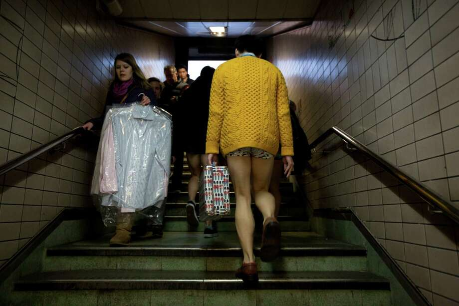 "A man taking part in the ""No Trousers Tube Ride"" event walks past a woman carrying laundered shirts on the stairs in Paddington Station, London, Sunday, Jan. 12, 2014.  The stunt was held to coincide with the ""Global No Pants Subway Ride"", where passengers board subway cars in the middle of winter without wearing trousers and act normally. Photo: Matt Dunham, AP  / AP"