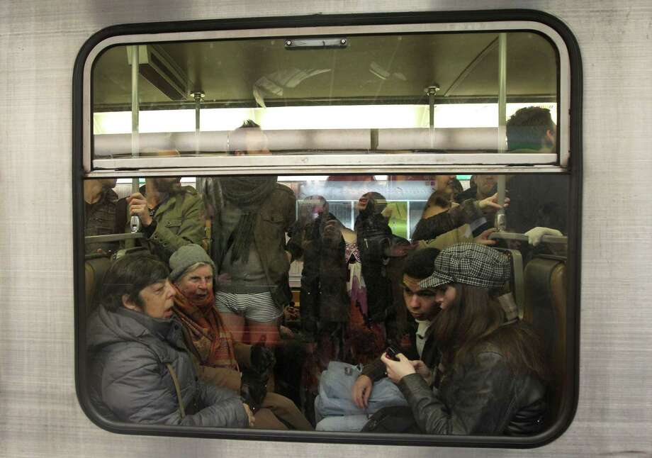A participant with no pants stands in a metro carriage, as he takes part in the 'No Pants Metro Ride' in Brussels, Sunday, Jan. 12, 2014. The idea started years ago as a small prank in New York and has grown into an international celebration of silliness, with dozens of cities around the world participating each year. Photo: Yves Logghe, AP  / AP