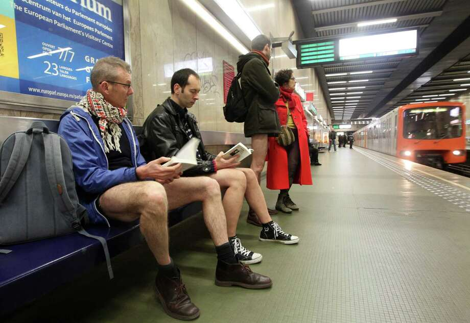 Participants read a book as they wait to take the metro,  during the 'No Pants Metro Ride' in Brussels, Sunday, Jan. 12, 2014. The idea started years ago as a small prank in New York and has grown into an international celebration of silliness, with dozens of cities around the world participating each year. Photo: Yves Logghe, AP  / AP