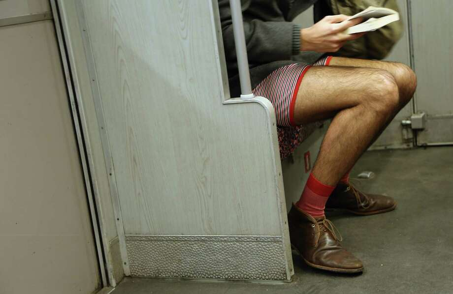 A participant of the No Pants Subway Ride reads a book while riding a train on January 12, 2014 in Berlin, Germany. The annual event, in which participants board a subway car in January while not wearing any pants while behaving as though they do not know each other, began as a joke by the public prank group Improv Everywhere in New York City and has since spread around the world, with enthusiasts in around 60 cities and 29 countries across the globe, according to the organization's site. Photo: Adam Berry, Getty Images / 2014 Getty Images