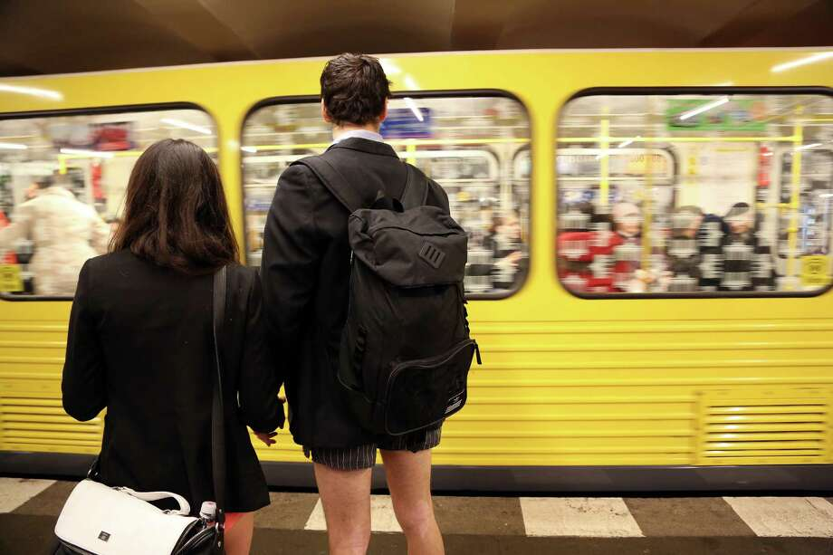 Participants of the No Pants Subway Ride hold hands as a train approaches on January 12, 2014 in Berlin, Germany. The annual event, in which participants board a subway car in January while not wearing any pants while behaving as though they do not know each other, began as a joke by the public prank group Improv Everywhere in New York City and has since spread around the world, with enthusiasts in around 60 cities and 29 countries across the globe, according to the organization's site. Photo: Adam Berry, Getty Images / 2014 Getty Images