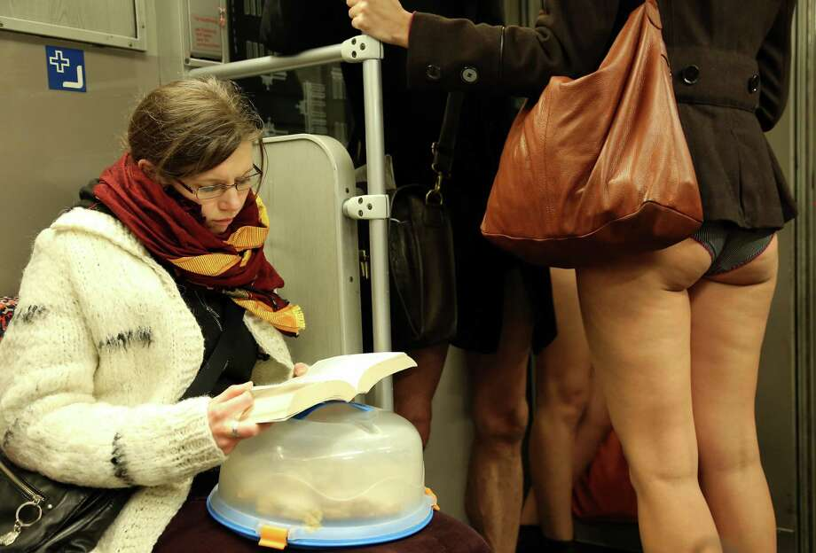 BERLIN, GERMANY - JANUARY 12:  An unsuspecting subway passenger reads a book next to participants of the No Pants Subway Ride on January 12, 2014 in Berlin, Germany. The annual event, in which participants board a subway car in January while not wearing any pants while behaving as though they do not know each other, began as a joke by the public prank group Improv Everywhere in New York City and has since spread around the world, with enthusiasts in around 60 cities and 29 countries across the globe, according to the organization's site. Photo: Adam Berry, Getty Images / 2014 Getty Images