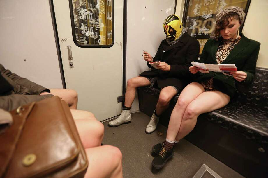 A participant of the No Pants Subway Ride wearing a luchador, or Mexican wrestler, mask sits next to another looking at a subway map as they ride a train on January 12, 2014 in Berlin, Germany. The annual event, in which participants board a subway car in January while not wearing any pants while behaving as though they do not know each other, began as a joke by the public prank group Improv Everywhere in New York City and has since spread around the world, with enthusiasts in around 60 cities and 29 countries across the globe, according to the organization's site. Photo: Adam Berry, Getty Images / 2014 Getty Images