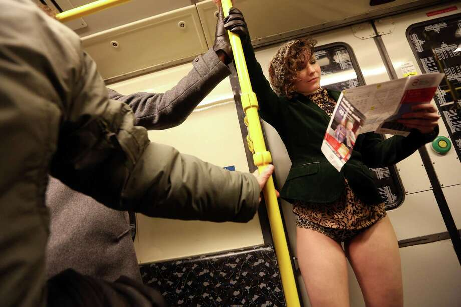 A participant of the No Pants Subway Ride looks at a subway map while riding a train on January 12, 2014 in Berlin, Germany. The annual event, in which participants board a subway car in January while not wearing any pants while behaving as though they do not know each other, began as a joke by the public prank group Improv Everywhere in New York City and has since spread around the world, with enthusiasts in around 60 cities and 29 countries across the globe, according to the organization's site. Photo: Adam Berry, Getty Images / 2014 Getty Images