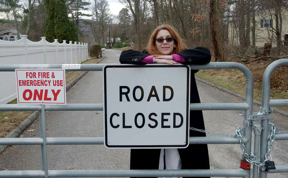 New Fairfield resident Elissa Boyet stands behind a gate that blocks access to her Squantz View Drive home from Carola Lane, in New Fairfield, Conn, on Sunday, January 12, 2014. Photo: H John Voorhees III / The News-Times Freelance