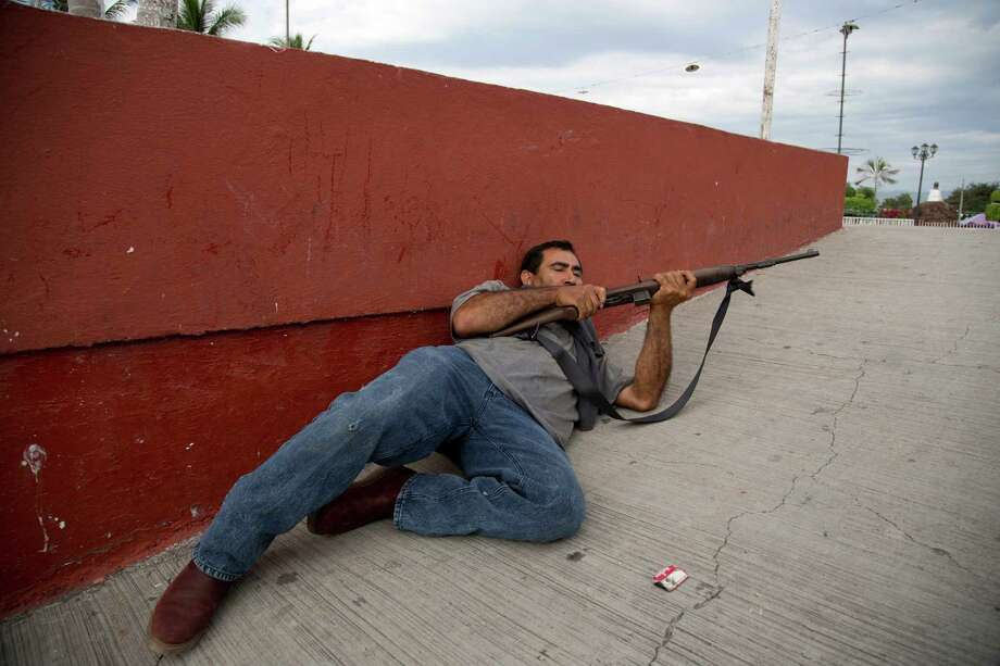 A man belonging to the Self-Defense Council of Michacan, (CAM), takes cover during a firefight while trying to flush out alleged members of the Knights Templar drug cartel from the town of Nueva Italia, Mexico, Sunday Jan. 12, 2014.  The vigilantes say they are liberating territory in the so-called Tierra Caliente and are aiming for the farming hub of Apatzingan, said to be the cartel's central command. Mexican military troops are staying outside the town and there are no federal police in sight. Photo: Eduardo Verdugo, AP  / AP