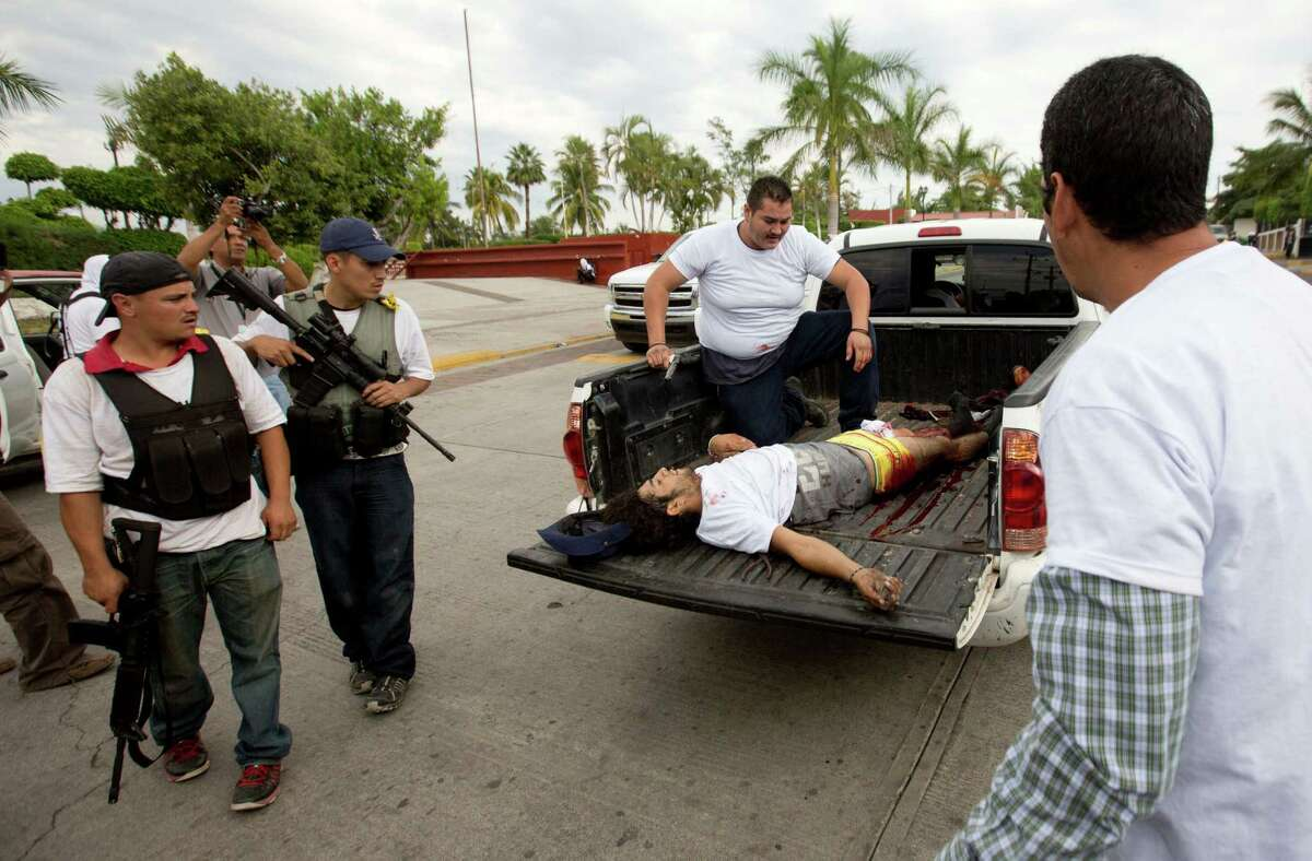 A wounded man belonging to the Self-Defense Council of Michacan, (CAM), is taken away during a firefight while trying to flush out alleged members of the Knights Templar drug cartel from the town of Nueva Italia, Mexico, Sunday Jan. 12, 2014. The vigilantes say they are liberating territory in the so-called Tierra Caliente and are aiming for the farming hub of Apatzingan, said to be the cartel's central command. Mexican military troops are staying outside the town and there are no federal police in sight.