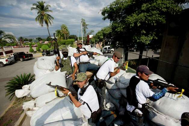 Men belonging to the Self-Defense Council of Michacan, (CAM), ride on a sandbag filled truck while trying to flush out alleged members of the Knights Templar drug cartel from the town of Nueva Italia, Mexico, Sunday Jan. 12, 2014.  The vigilantes say they are liberating territory in the so-called Tierra Caliente and are aiming for the farming hub of Apatzingan, said to be the cartel's central command. Mexican military troops are staying outside the town and there are no federal police in sight. Photo: Eduardo Verdugo, AP  / AP