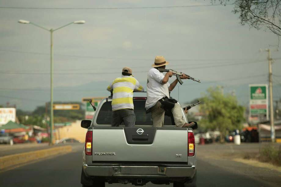 Men belonging to the Self-Defense Council of Michacan, (CAM), ride on a pick-up truck while trying to flush out alleged members of the Knights Templar drug cartel from the town of Nueva Italia, Mexico, Sunday Jan. 12, 2014.  The vigilantes say they are liberating territory in the so-called Tierra Caliente and are aiming for the farming hub of Apatzingan, said to be the cartel's central command. Mexican military troops are staying outside the town and there are no federal police in sight. Photo: Eduardo Verdugo, AP  / AP