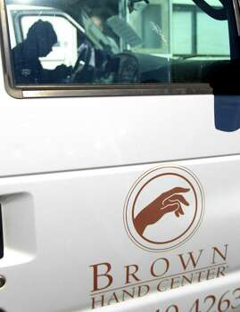 Robert Washington sits in the 2006 Ford E350 van with the Brown Hand Center logo, on display before bidding began at Webster's Auction Palace,Sunday, Jan. 12, 2014, in Houston, during the second of four Sunday auctions of the late Dr. Michael Brown's estate.  The sale of his items are part of a bankruptcy case still in progress in U.S. District Court. Items this time included vehicles, tools, machinery, restaurant equipment and two trailer-mounted generators. Photo: Karen Warren, Houston Chronicle / © 2013 Houston Chronicle