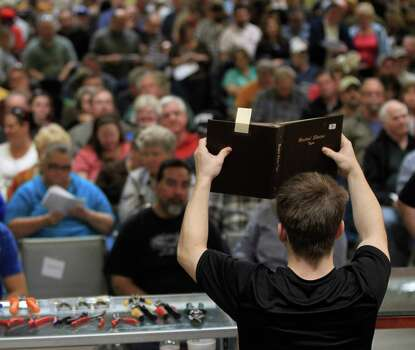 A book of coins is hoisted up for bidders to see at Webster's Auction Palace,Sunday, Jan. 12, 2014, in Houston.  This is the second of four Sunday auctions of the late Dr. Michael Brown's estate.  The sale of his items are part of a bankruptcy case still in progress in U.S. District Court. Items this time included vehicles, tools, machinery, restaurant equipment and two trailer-mounted generators. Photo: Karen Warren, Houston Chronicle / © 2013 Houston Chronicle