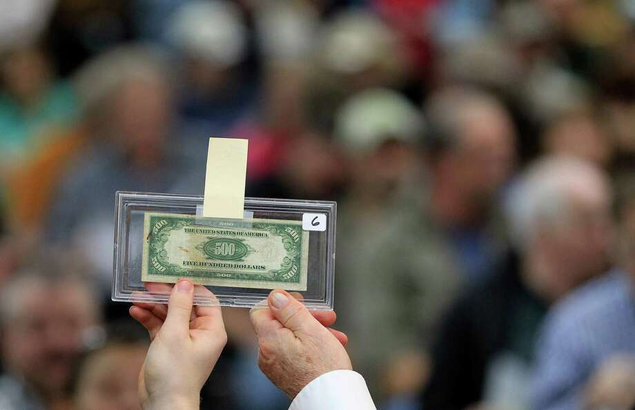 A $500 bill is hoisted up for bidders to see at Webster's Auction Palace,Sunday, Jan. 12, 2014, in Houston.  This is the second of four Sunday auctions of the late Dr. Michael Brown's estate.  The sale of his items are part of a bankruptcy case still in progress in U.S. District Court. Items this time included vehicles, tools, machinery, restaurant equipment and two trailer-mounted generators. Photo: Karen Warren, Houston Chronicle / © 2013 Houston Chronicle