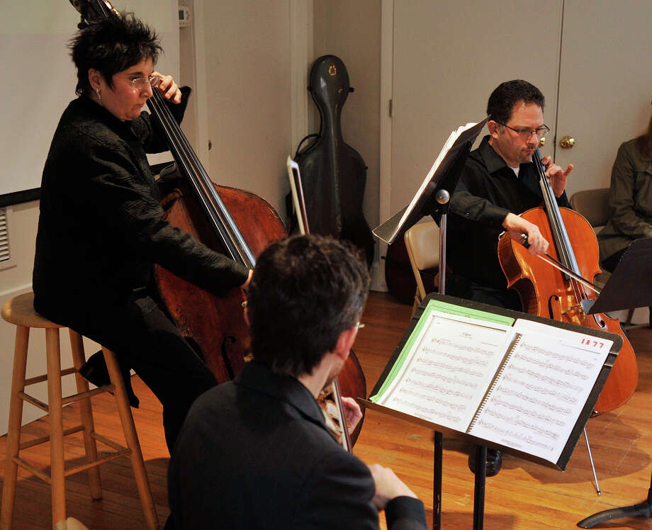Robert Zubrycki, center foreground, plays the violin, Judith Sugarman, left, plays the bass and Peter Sanders plays on the cello during the Exploring the Orchestra series with musicians with the Stamford Symphony at the Stamford Museum & Nature Center in Stamford, Conn., on Sunday, Jan. 12, 2014. Sunday's presentation focused on The Case of the Suspicious Strings. On Feb. 2, the series with continute with The Case of the Worried Woodwinds and on March 9, is The Case of the Brilliant Brass. Photo: Jason Rearick / Stamford Advocate