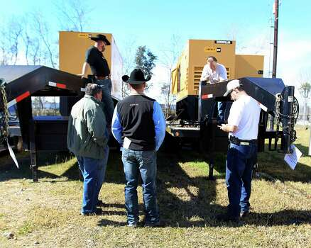 Potential buyers look at two D200P3 Caterpillar Olympian Trailer Mounted Electric Generators at Webster's Auction Palace,Sunday, Jan. 12, 2014, in Houston.  This is the second of four Sunday auctions of the late Dr. Michael Brown's estate.  The sale of his items are part of a bankruptcy case still in progress in U.S. District Court. Items this time included vehicles, tools, machinery, restaurant equipment and two trailer-mounted generators. Photo: Karen Warren, Houston Chronicle / © 2013 Houston Chronicle