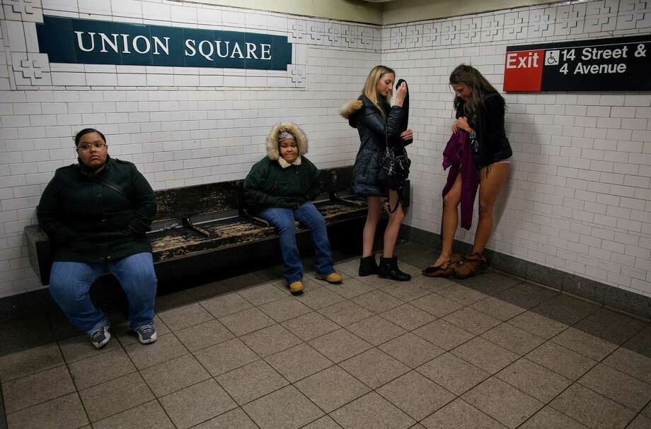 Marianne Cornejo, far right, and Leah Estreicher, center right, both of New York, start to get dressed at the Union Square subway station after participating in the annual No Pants Subway Ride, Sunday, Jan. 12, 2014, in New York. The staged event, organized by the group Improv Everywhere, invited people onto the subways without pants to act out what might be a normal commute. Photo: Craig Ruttle, AP / FR61802 AP