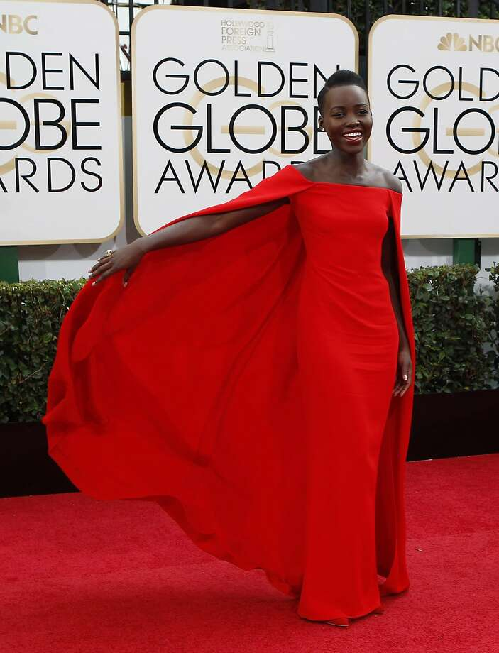 Lupita Nyong'o draws admiring attention sweeping into the show in her dramatically caped silk crepe Ralph Lauren. Photo: Wally Skalij, McClatchy-Tribune News Service