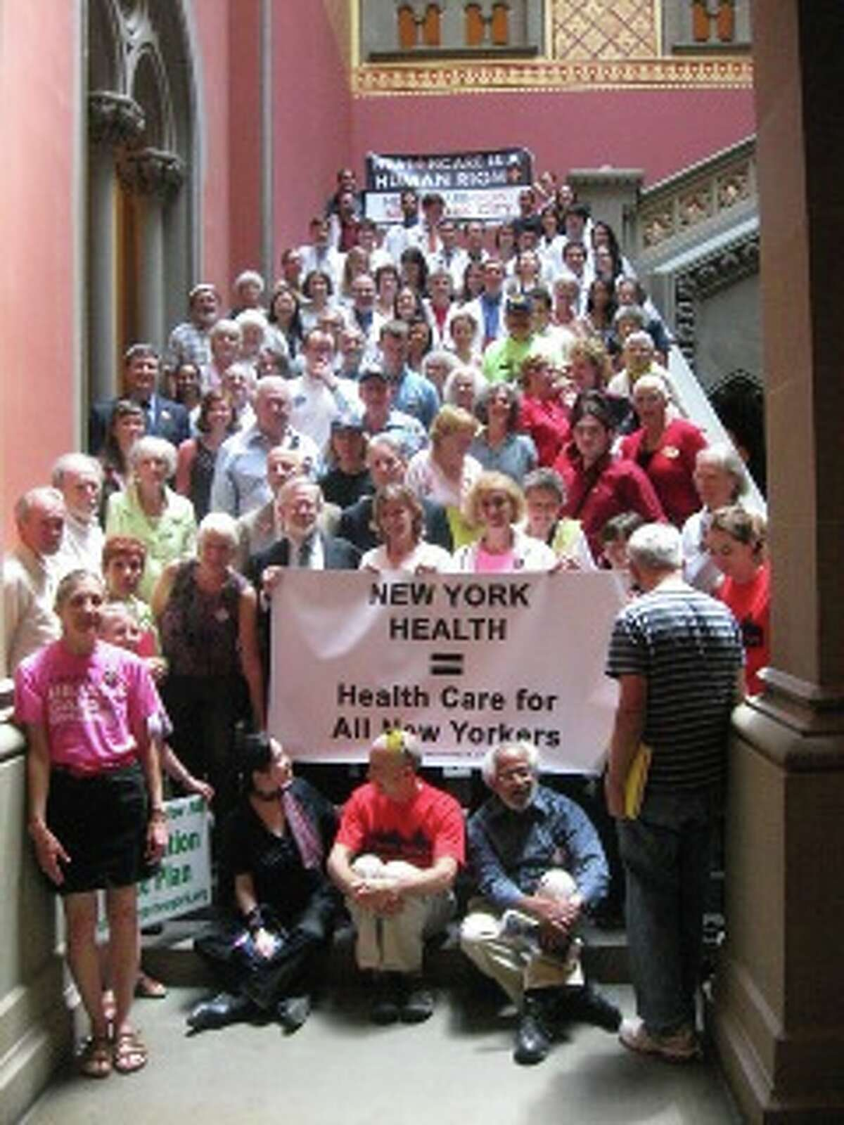A coalition of groups supporting universal health coverage lobbied the Capitol in May. Assemblyman Richard Gottfried (D-Manhattan) is pictured on the left corner of the sign. (Photo: Alice Brody)