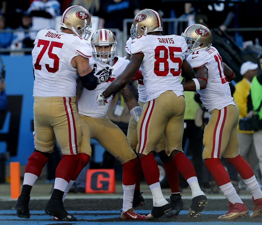Colin Kaepernick (7) is surrounded by teammates after his third quarter touchdown Sunday January 12, 2014. The San Francisco 49ers beat the Carolina Panthers 23-10 in Charlotte, North Carolina to advance to the NFC title game against Seattle. Photo: Brant Ward, The Chronicle
