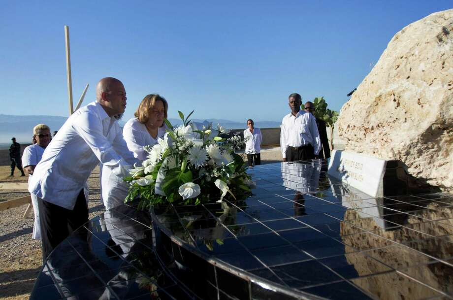 Haiti's President Michel Martelly, left, and first lady Sophia Martelly, center, place a bouquet of flowers at a monument in memory of the victims of the 2010 earthquake, during a memorial service at Titanyen, a mass burial site for earthquake victims, north of Port-au-Prince, Haiti, Sunday, Jan. 12, 2014. Martelly's government issued a decree declaring Jan. 12 a day of remembrance and reflection. The Haitian flag is being flown at half-staff, and clubs are to remain closed. (AP Photo/Jean Marc Herve Abelard) Photo: Jean Marc Herve Abelard, STR / AP