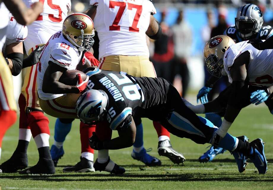 Charles Johnson (95) tackles Frank Gore (21). Photo: David T. Foster III, McClatchy-Tribune News Service