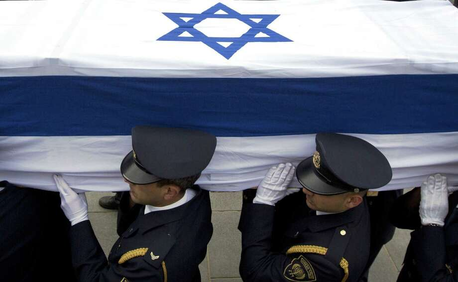 A Knesset honor guard carries the casket of late Israel Prime Minister Ariel Sharon, who died Saturday at 85, eight years after a stroke left him in a coma. Photo: Sebastian Scheiner / Associated Press / AP