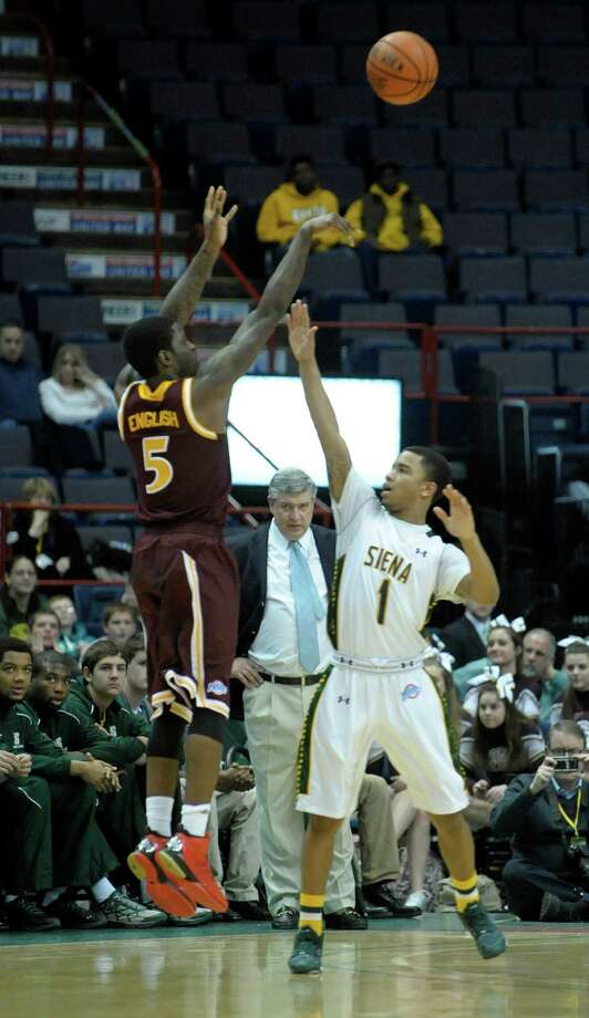 Iona's A.J. English puts up a shot as Siena's Marquis Wright tries to defend as Siena's coach, Jimmy Patsos, background, looks on during the Siena Iona men's basketball game on Sunday, Jan. 12, 2014 in Albany, NY.   (Paul Buckowski / Times Union) Photo: Paul Buckowski / 00025111E