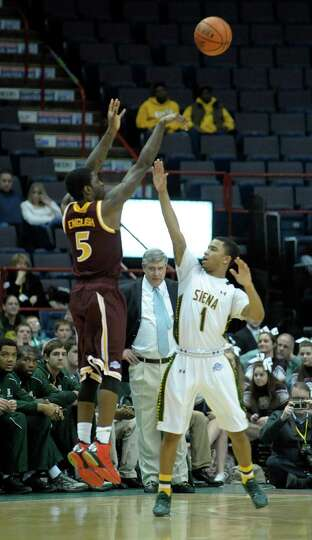 Iona's A.J. English puts up a shot as Siena's Marquis Wright tries to defend as Siena's coach, Jimmy