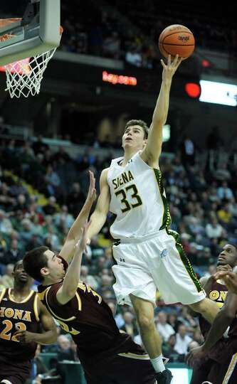 Iona's Ryden Hines, left, fouls Siena's Rob Poole  during the Siena Iona men's basketball game on Su
