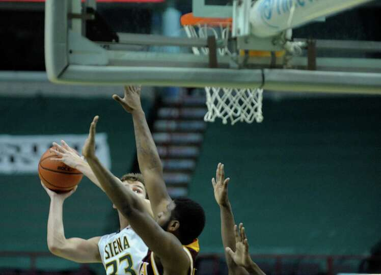 Siena's Rob Poole, left, puts up a shot over Iona defenders during the Siena Iona men's basketball g