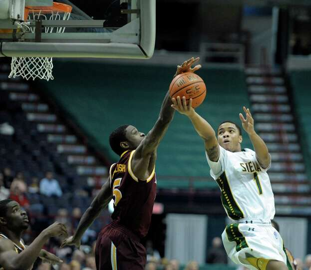 Iona's A.J. English, left, blocks the shot attempt by Siena's Marquis Wright during the Siena Iona m