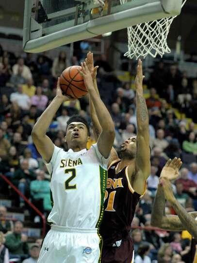 Siena's Javion Ogunyemi, left, puts up a shot over Iona defenders during the Siena Iona men's basket