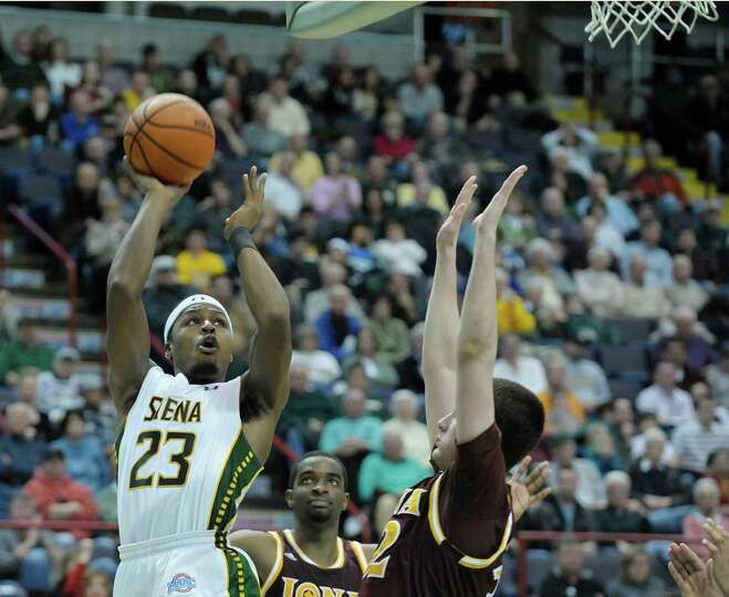 Siena's Maurice White puts up a shot over Iona defenders during the Siena Iona men's basketball game